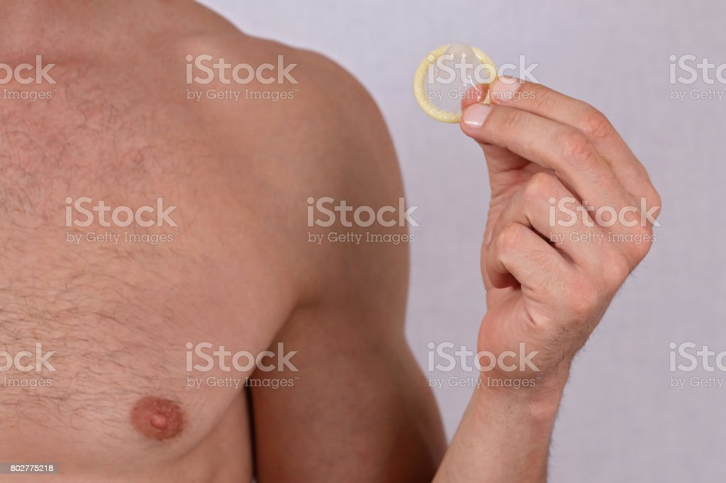 Man holding condom close up. Contraception, Prevention of sexually transmitted diseases. Sexual health concept. stock photo