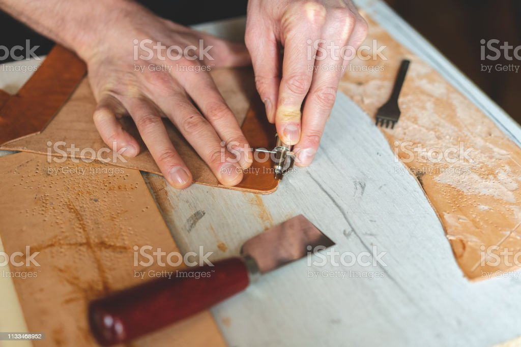 Working process in the leather workshop. Man holding crafting tool...