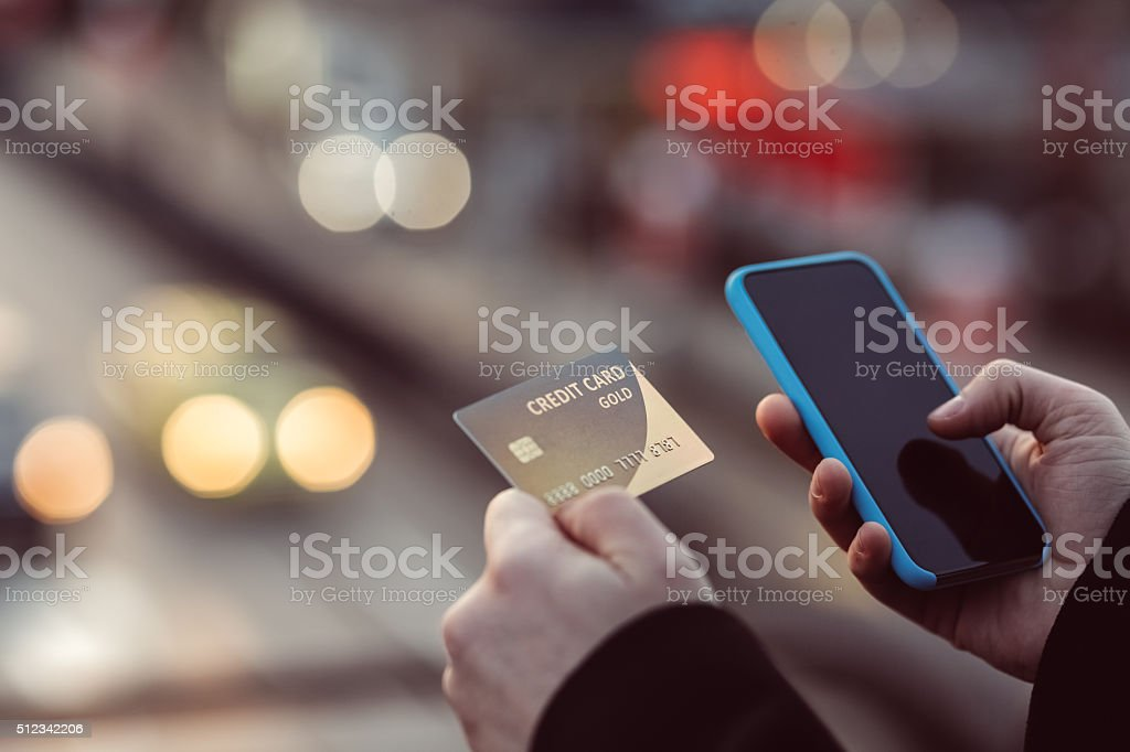 Man holding credit card and texting stock photo