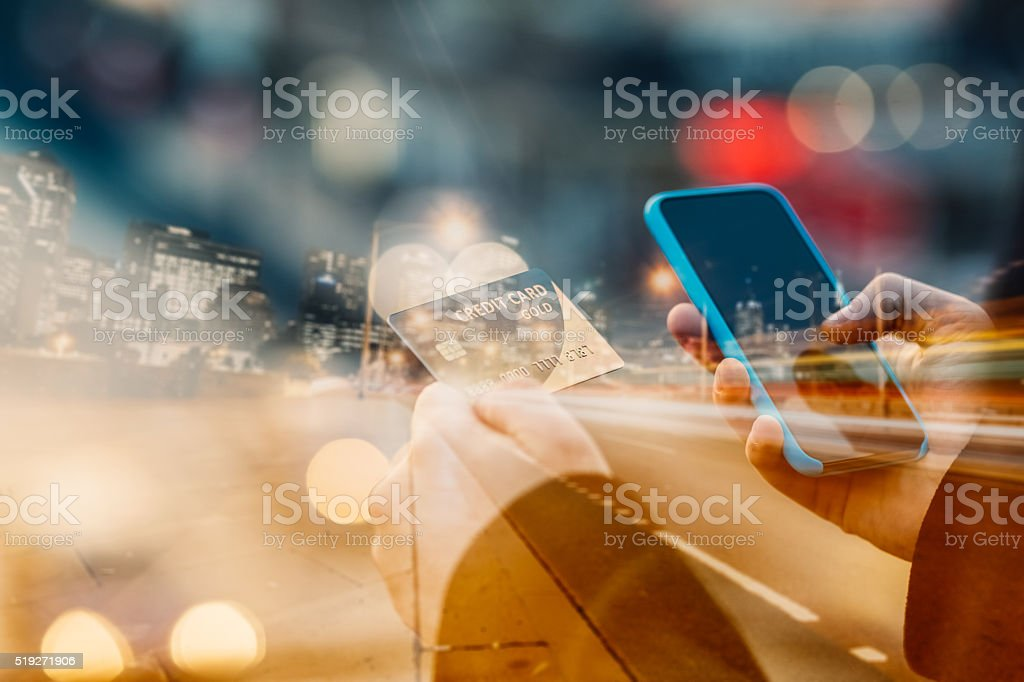 Man holding credit card and texting bildbanksfoto