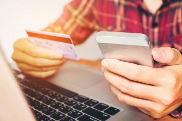 mann hält kreditkarte und mittels handy holding kreditkarte mit online-shopping - free online game stock-fotos und bilder