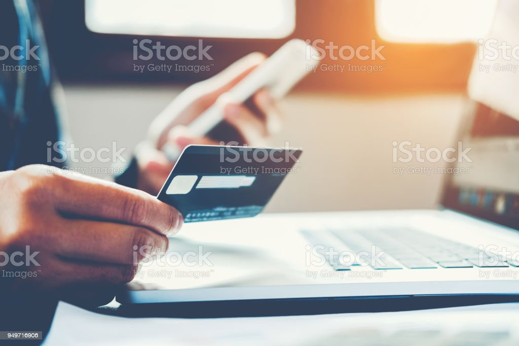 Man Holding Credit Card And Using Cell Phone holding credit card with shopping online stock photo