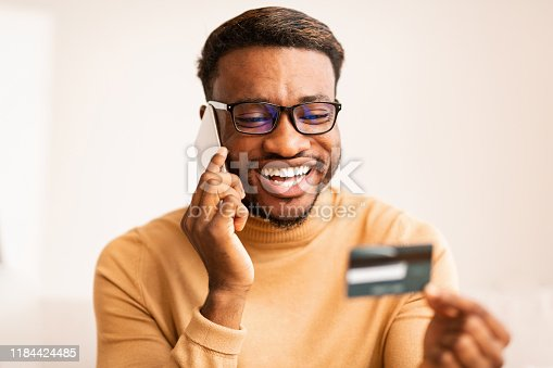 1173546354 istock photo Man Holding Credit Card Consulting On Phone At Home 1184424485