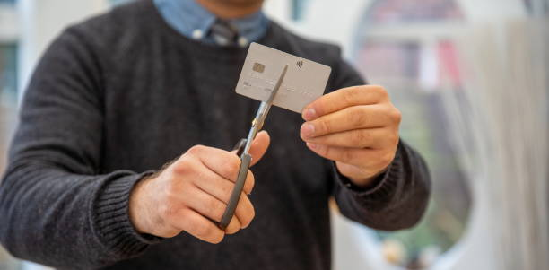 man holding credit card cut into halves and looking happy debt payout. cutting credit card. Man cutting debit card scissors Hands of man cutting a credit card with scissors. financial problems at home stock photo