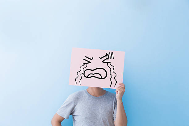 man holding crying expression billboard - sad cartoon images stock photos and pictures