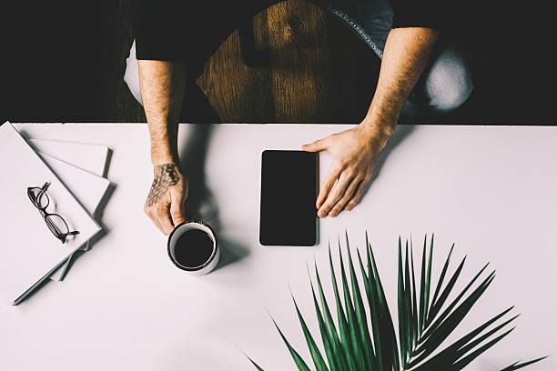 man holding cup of coffee and tablet on office desk - kaffeetasse tattoo stock-fotos und bilder
