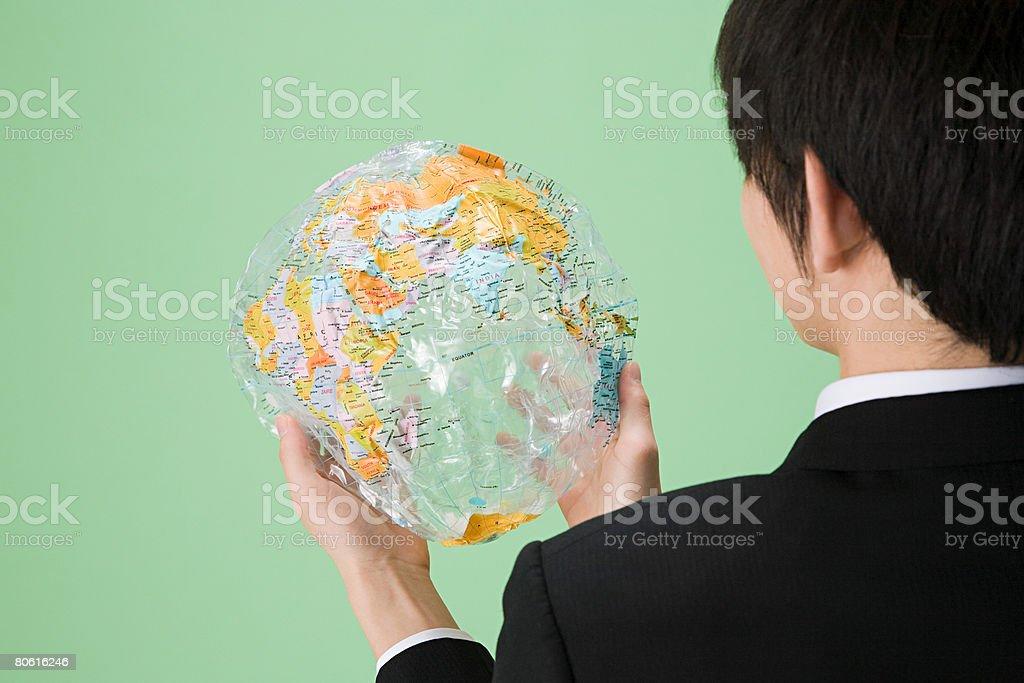 Man holding deflated globe royalty-free stock photo