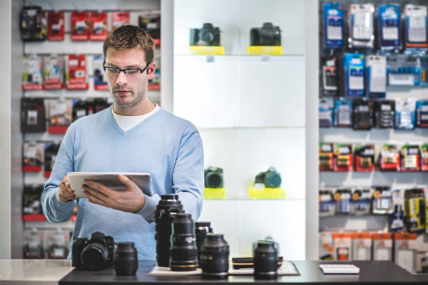 man holding digital tablet in the store - sale lenses stock photos and pictures