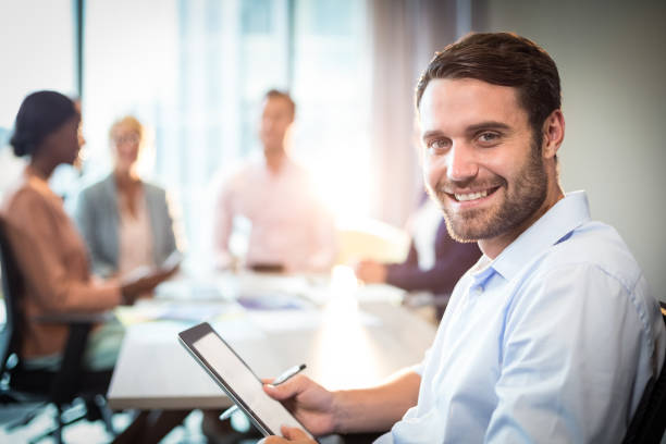 Man holding digital tablet while coworker interacting in the background stock photo