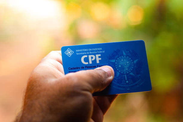 Man holding document  - Cadastro de Pessoa Física - (CPF). The document guarantees authenticity and integrity in electronic communication between people in Brazil Man holding document  - Cadastro de Pessoa Física - (CPF). The document guarantees authenticity and integrity in electronic communication between people in Brazil. between stock pictures, royalty-free photos & images
