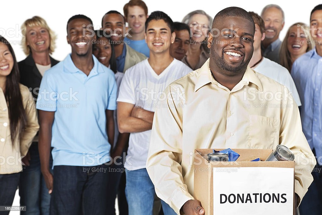 Man holding donation box with group behind him royalty-free stock photo