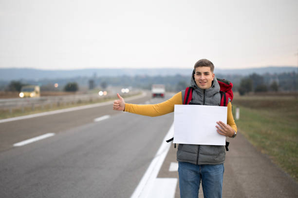 Man holding empty cardboard while hitchhiking stock photo