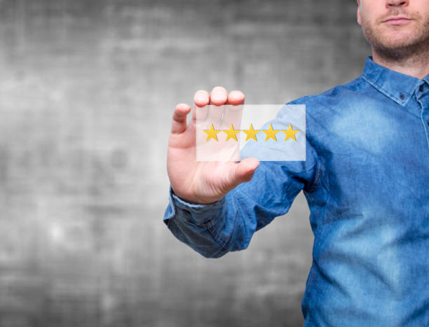Man holding five star rating. Five stars service. Grey background - Stock Image stock photo