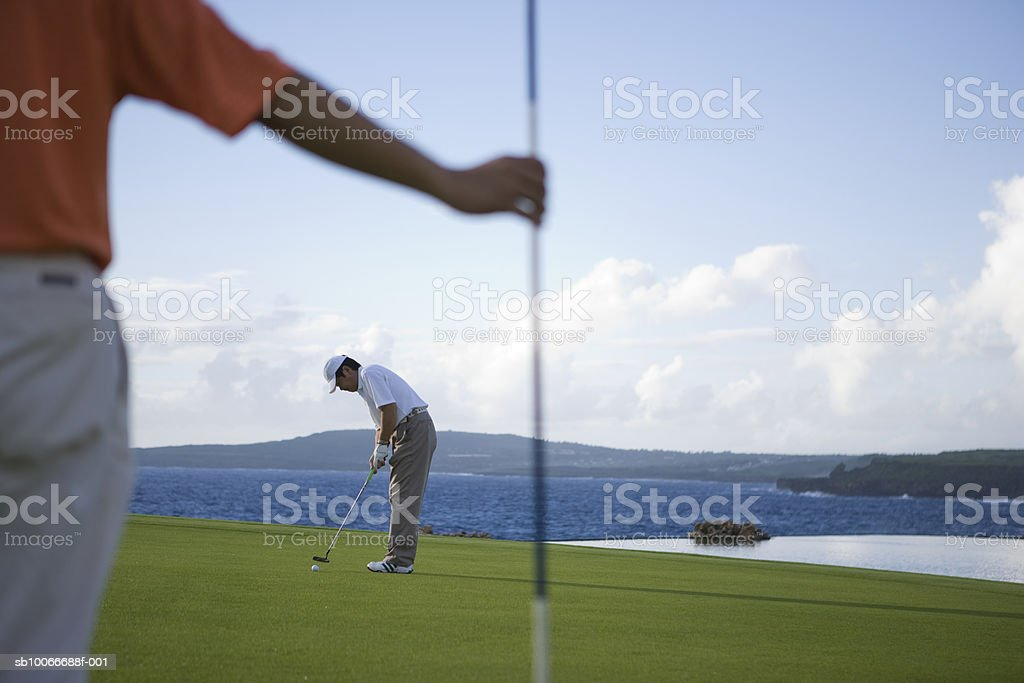 Man holding flag and other golfer putting golf ball (focus on background) 免版稅 stock photo