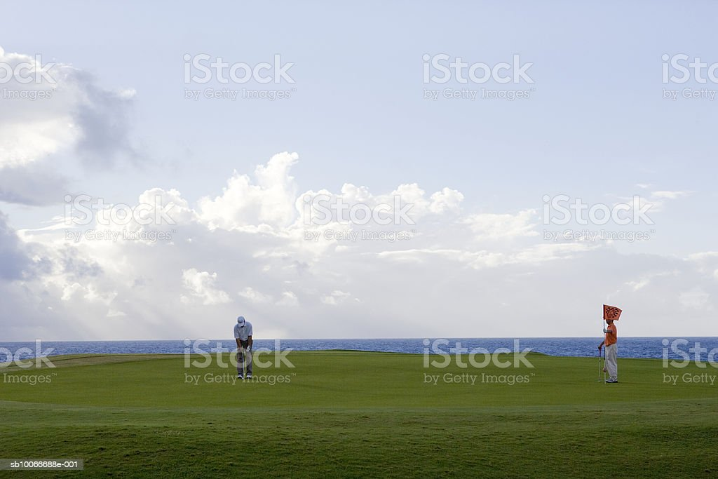 Man holding flag and other golfer putting royalty-free stock photo