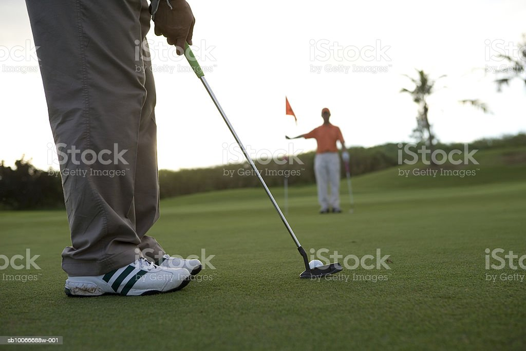 Man holding flag and other golfer putting (focus on foreground) royalty-free stock photo