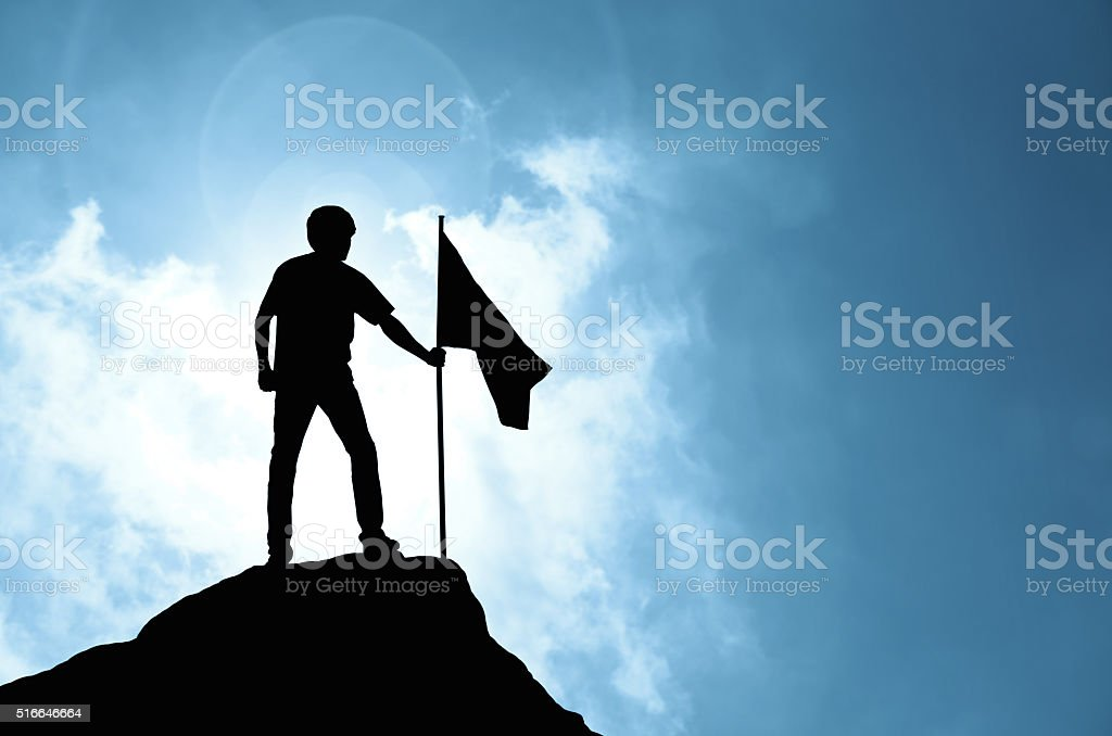 Man holding flag on peak of mountain stock photo