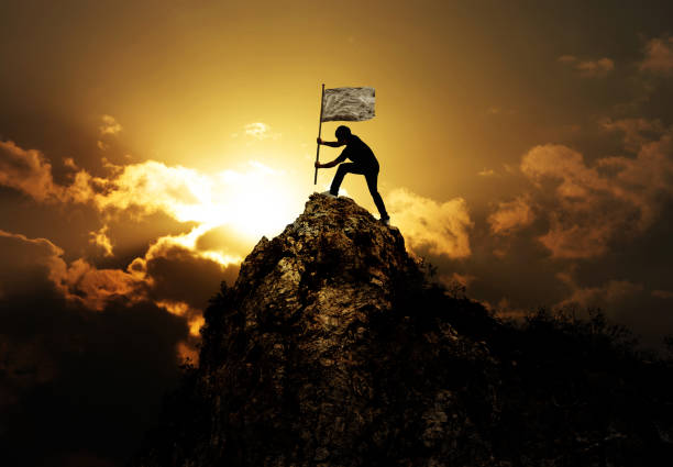 Man holding flag on the peak of mountain and sunset stock photo
