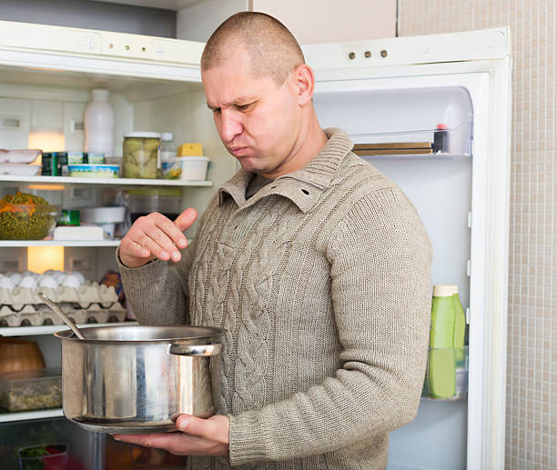 Man holding foul food Man holding foul food near refrigerator addle stock pictures, royalty-free photos & images