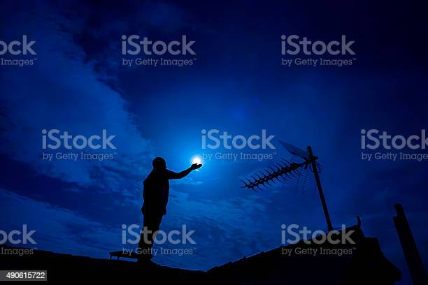 Photo of Man holding full moon in hand against night sky