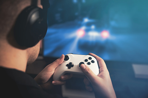 istock Man holding game pad and playing car race game 1131624458