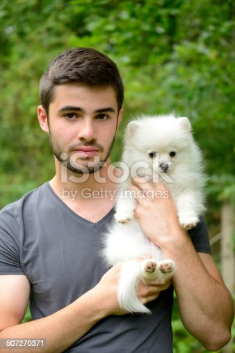 istock Man holding german spitz puppy outside and looking at camera. 507270371