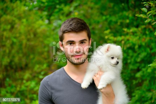 istock Man holding german spitz puppy outside and looking at camera. 507270375