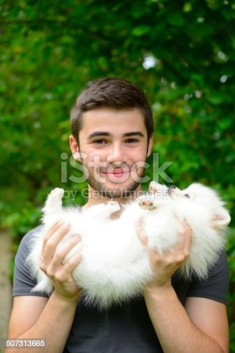 istock Man holding german spitz puppy outside and looking at camera. 507313665
