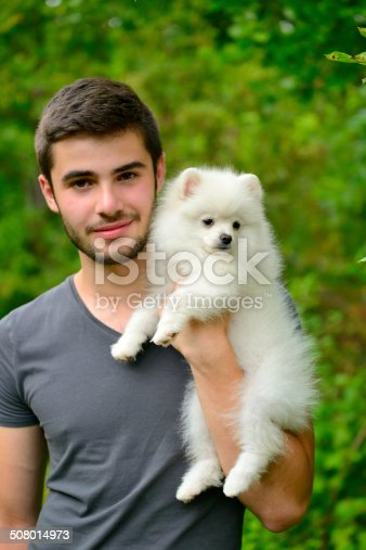 istock Man holding german spitz puppy outside and looking at camera. 508014973