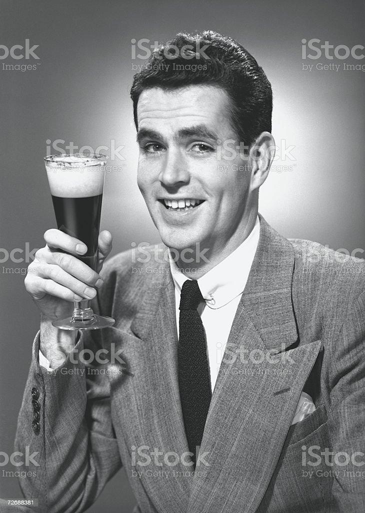 Man holding glass of beer in studio, (B&W), portrait stock photo