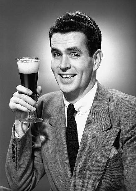 Man holding glass of beer in studio, (B&W), portrait stock photo