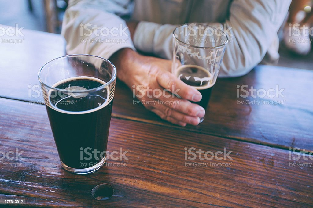 Man holding glass of stout beer on rustic table top stock photo
