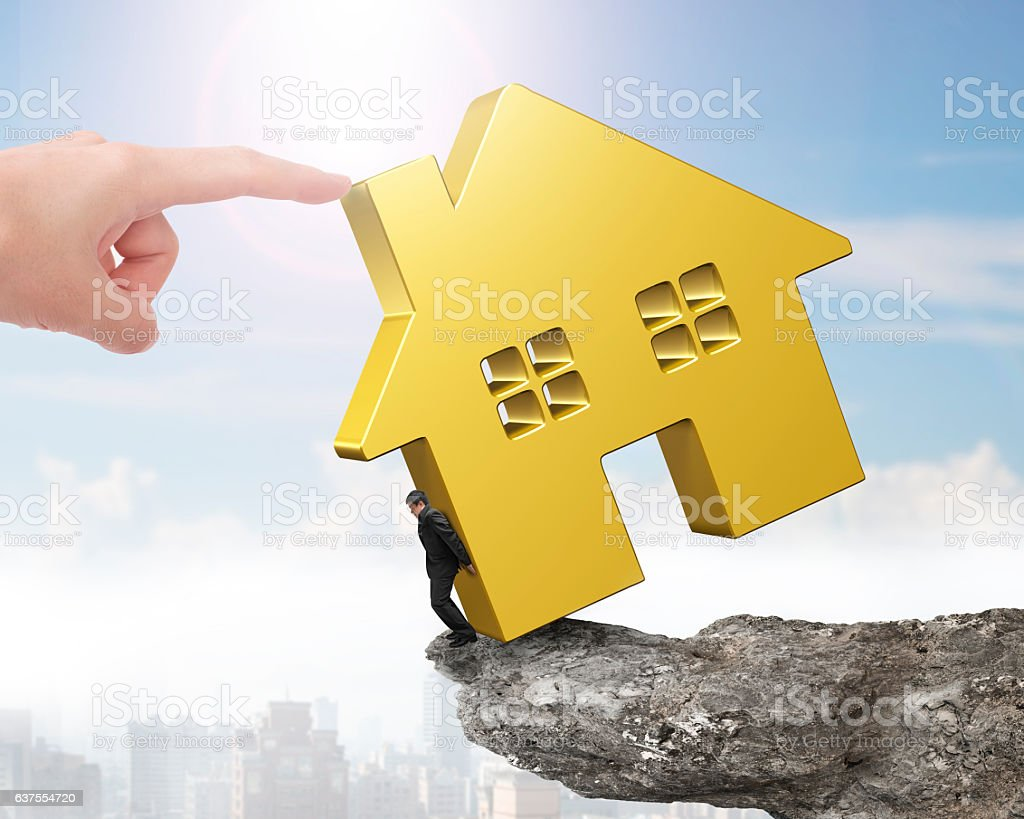 Man holding golden house on cliff edge with hand pushing stock photo