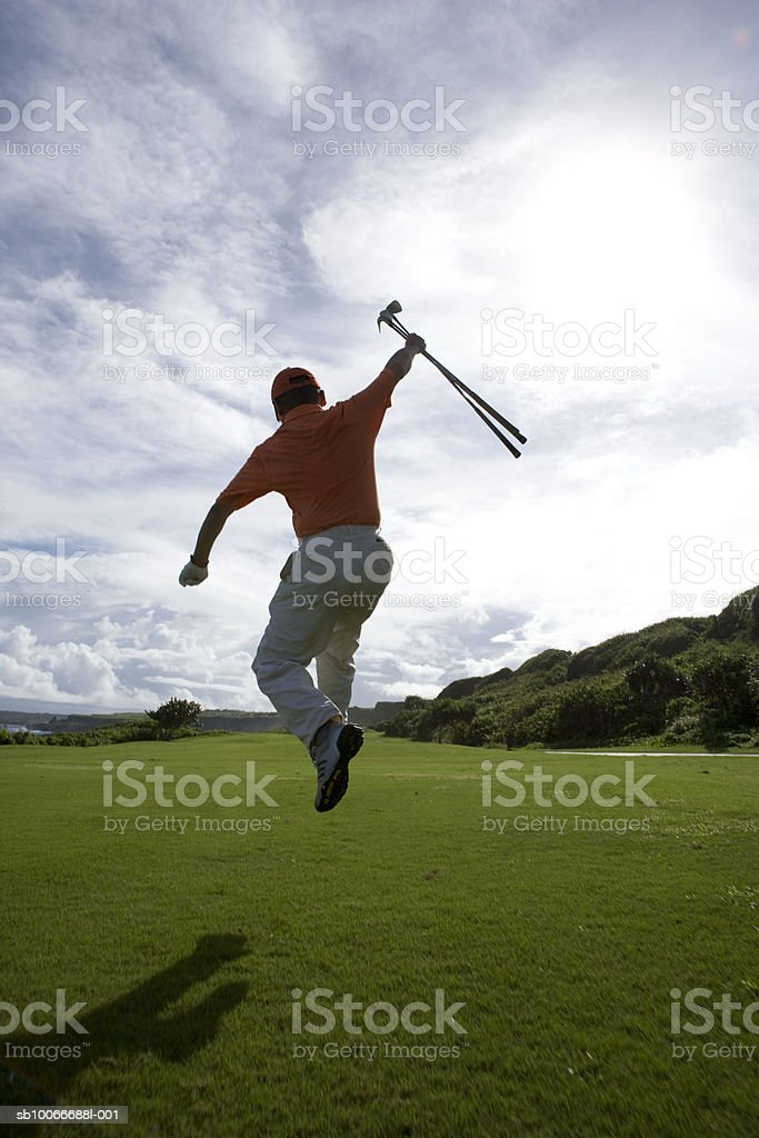 Man holding golf club and jumping, rear view royalty-free stock photo