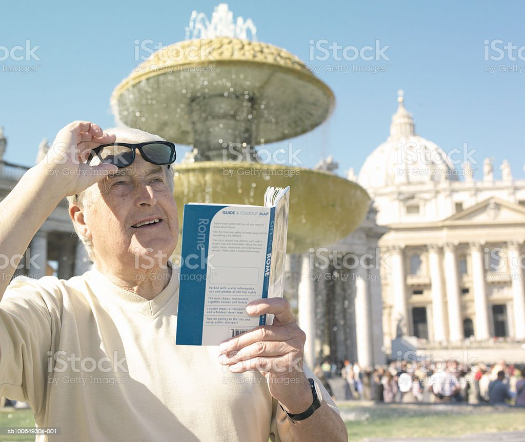 Man holding guidebook, looking up photo libre de droits