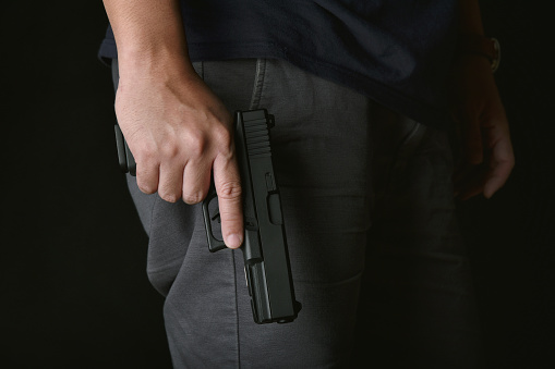 istock Man holding gun close to the body, Killer with 9mm handgun pistol waiting for robbing the victim, Weapon and violence crime concept.A 1215637919