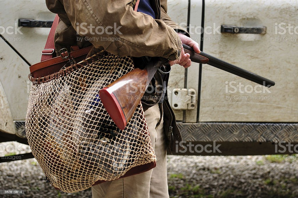 Man holding gun with a game bag full of birds royalty-free stock photo