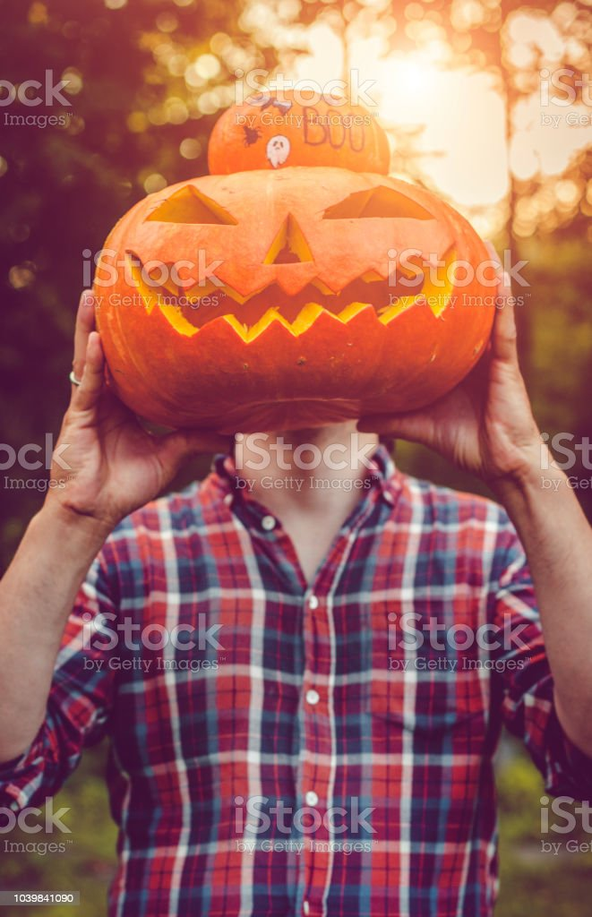 Man holding Halloween jack o' lantern  pumpkin stock photo