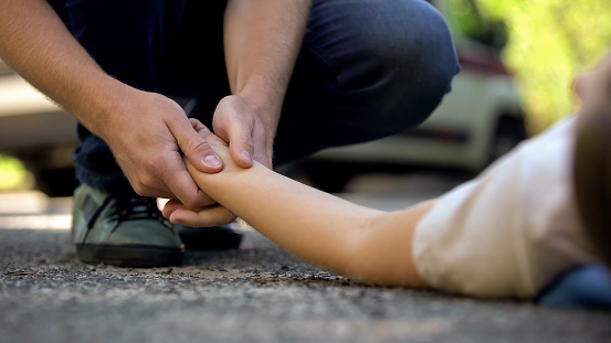 istock Man holding hand of girl lying on road, unconscious victim of car accident, 911 1131889191