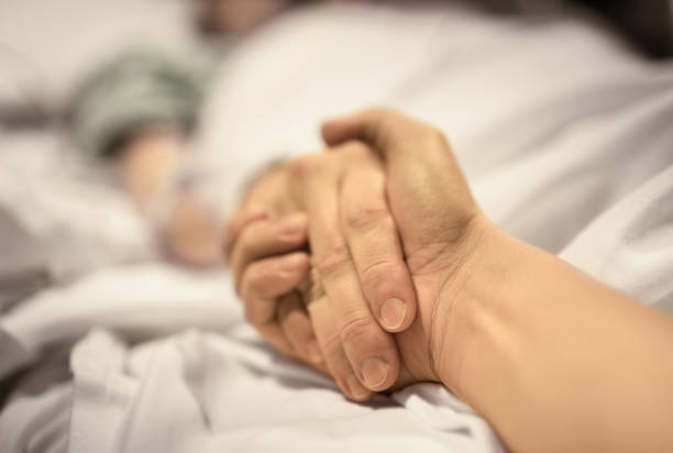 Man holding hand of woman in the hospital stock photo