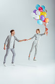 man holding hand of woman jumping in air with bundle of colorful balloons on grey background