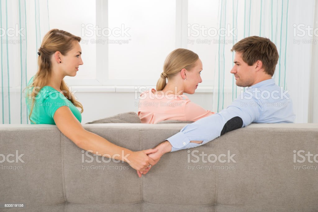 Man Holding Hands Of Other Female While Looking At Girlfriend stock photo