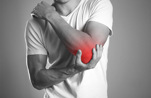 istock A man holding hands. Pain in the elbow. The hearth is highlighted in red. Close up. Isolated background 1053331028