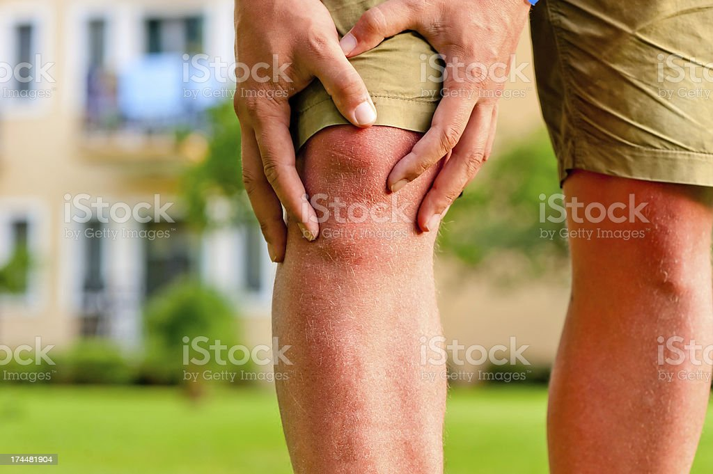 man holding hands sore knee stock photo
