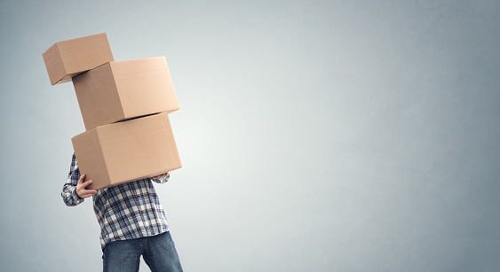 istock Man holding heavy cardboard boxes relocation, moving house or courier delivery 1200124376