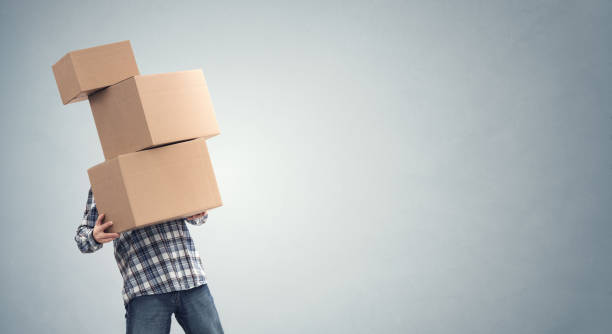 Man holding heavy cardboard boxes relocation, moving house or courier delivery stock photo