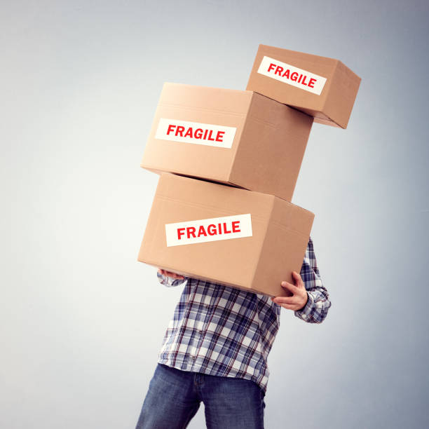 Man holding heavy fragile cardboard boxes relocation, moving house or courier delivery stock photo