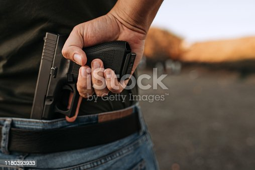 Man holding hidden short gun in his hand.