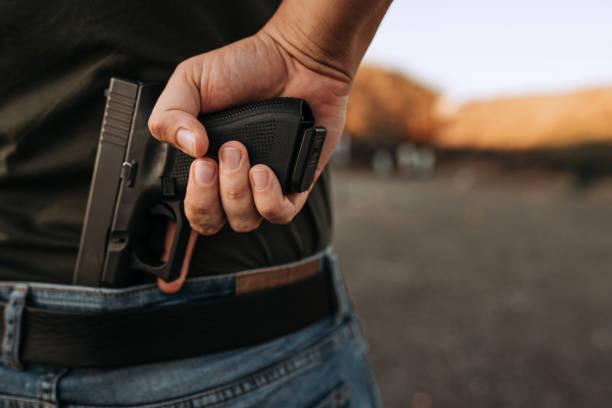 El hombre sosteniendo un arma corta escondida en su mano. - foto de stock