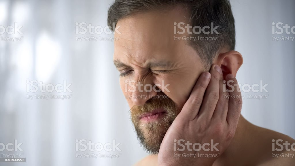 Man holding his aching ear, suffering from otitis, sudden hearing...
